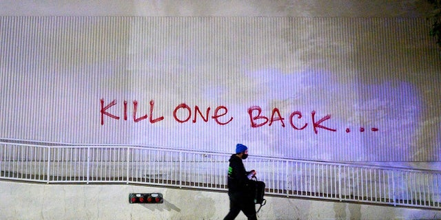 A demonstrator passes graffiti in Oakland, Calif. while protesting the death of George Floyd. (AP Photo/Noah Berger)