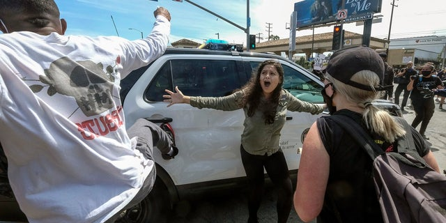 A protester, center, tries to stop others from attacking a police vehicle during a protest over the death of George Floyd in Los Angeles on Saturday. (AP Photo/Ringo H.W. Chiu)