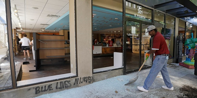 A worker sweeps broken glass from a window at the Louisville Visitors Center, early Saturday, May 30, 2020, in Louisville, Ky. The window was broken Friday evening during a protest over the deaths of George Floyd and Breonna Taylor. (AP Photo/Darron Cummings)