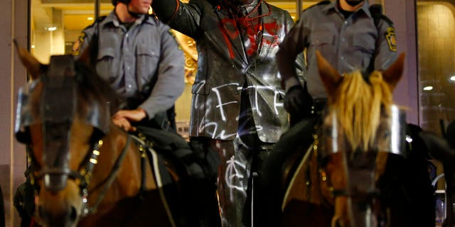 A vandalized statue of the late Philadelphia Mayor Frank Rizzo, who also served as the city's police commissioner, stands behind mounted State Police officers outside the Municipal Services Building in Philadelphia, The statue was vandalized during a protest over the death of George Floyd, a black man who died in Minneapolis police custody on May 25.