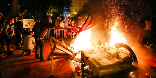 Demonstrators start a fire as they protest the death of George Floyd, Sunday, May 31, 2020, near the White House in Washington. (AP Photo/Alex Brandon)