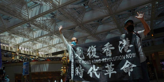 "Protesters gesture with five fingers, signifying the ""Five demands - not one less"" in a shopping mall during a protest against China's national security legislation for the city, in Hong Kong, Monday, June 1, 2020."