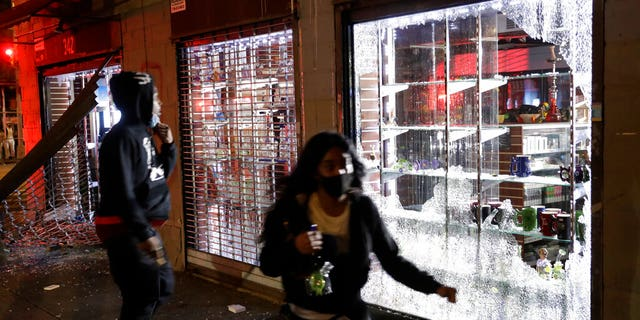 People run as police arrive to the scene of a broken into smoke shop in New York, Monday, June 1, 2020. A fourth day of protests against police brutality kept New York City on edge Sunday, as thousands of people marched and many protesters and officers tried to keep the peace after days of unrest that left police cars burned and hundreds of people under arrest. (AP Photo/Seth Wenig)