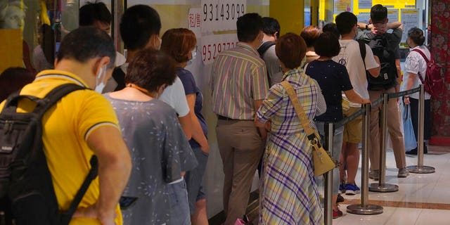 People queue up outside the DHL Express store in Hong Kong, Monday, June 1, 2020.