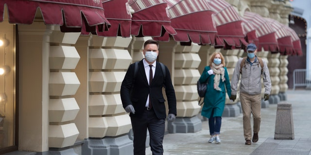People wearing face masks and gloves to protect from coronavirus, walk to an entrance of the GUM, State Department store after reopening in Moscow, Russia, on Monday, June 1, 2020. Monday's reopening of retail stores along with dry cleaners and repair shops comes as the pace of contagion has stabilized in the Russian capital that has accounted for about half of the nation's infections.聽