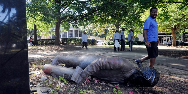 An unidentified man walks past a toppled statue in Birmingham, Ala., on Monday, June 1, 2020, following a night of unrest. People shattered windows, set fires and damaged monuments in a downtown park after a protest against the death of George Floyd. Floyd died after being restrained by Minneapolis police officers on May 25. (AP Photo/Jay Reeves)