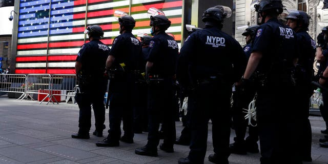 Police officers in riot gear stand by in Times Square during a protest in Manhattan in New York, Monday, June 1, 2020. New York City imposed an 11 p.m. curfew Monday as the nation's biggest city tried to head off another night of destruction erupting amid protests over George Floyd's death.