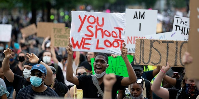 People carry signs as they march Monday, June 1, 2020, in Atlanta during a demonstration over the death of George Floyd, who died after being restrained by Minneapolis police officers on May 25. (AP Photo/John Bazemore).