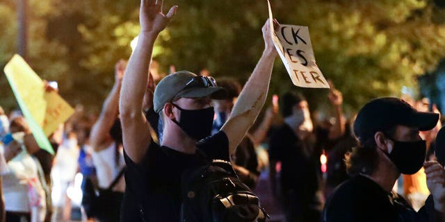 A protester raises his hands over the deaths of George Floyd and Breonna Taylor, Monday, June 1, 2020, in Louisville, Ky. Taylor, a black woman, was fatally shot by police in her home in March and Floyd, a black man, died after being restrained by Minneapolis police officers on May 25.