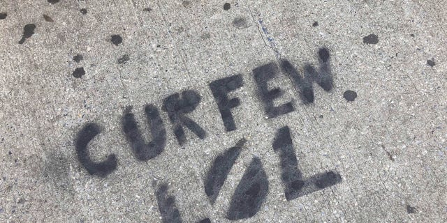 A sidewalk is spray painted with graffiti about New York City's curfew order, in the Brooklyn borough of New York, Tuesday, June 2, 2020.  (AP Photo/Mark Lennihan)