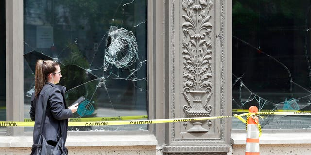 A woman walks past broken windows, Tuesday, June 2, 2020, in downtown Cleveland.