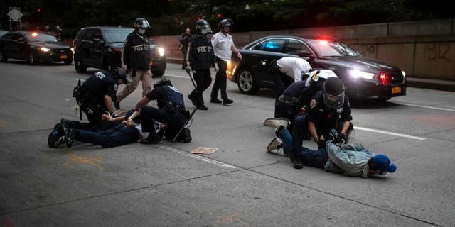 Police arrest protesters refusing to get off the streets during an imposed curfew while marching in a rally calling for justice over the death of George Floyd Tuesday, June 2, 2020, in New York. Floyd died after being restrained by Minneapolis police officers on May 25.