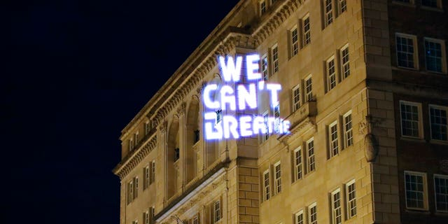 Demonstrators project the words 'we can't breathe' onto the front of the Hay Adams hotel as protests continue over the death of George Floyd, Wednesday, June 3, 2020, near the White House in Washington, D.C.