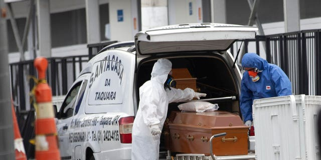 Funeral workers wearing protective gear as a precaution amid the new coronavirus pandemic push the remains of a COVID-19 victim into a funeral car at a field hospital in Rio de Janeiro.