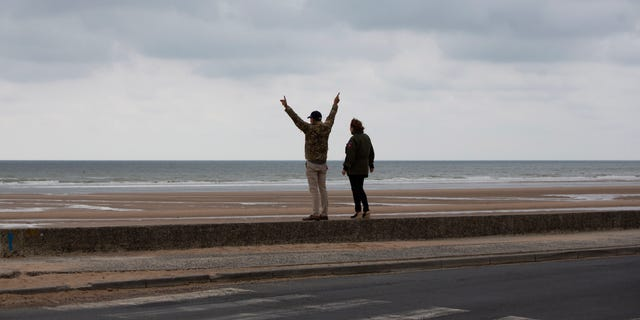 In this photo taken on Thursday, June 4, 2020, A man and woman in US military jackets stand in front of Omaha Beach in Saint-Laurent-sur-Mer, Normandy, France. In sharp contrast to the 75th anniversary of D-Day, this year's 76th will be one of the loneliest remembrances ever, as the coronavirus pandemic is keeping nearly everyone from traveling. (AP Photo/Virginia Mayo)