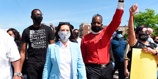 Michigan Gov. Gretchen Whitmer, center, marches with others, on Woodward during a rally in Highland Park, Thursday, June 4, 2020. (Clarence Tabb, Jr./Detroit News via AP)