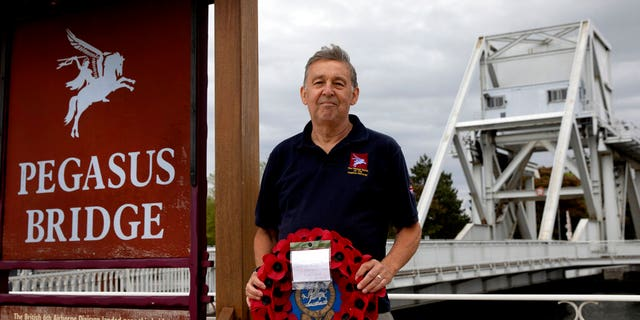 In this photo taken on Friday, June 5, 2020, British expatriate Steven Oldrid holds a poppy wreath as he stands on the site of the original WWII Pegasus Bridge in Benouville, Normandy, France. Due to coronavirus measures many relatives and veterans will not make this years 76th anniversary of D-Day. Oldrid will be bringing it to them virtually as he places wreaths and crosses for families and posts the moments on his facebook page.