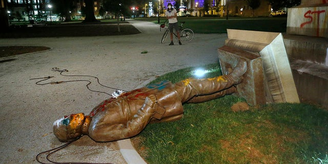 The statue of Confederate Gen. Williams Carter Wickham lies on the ground after protesters pulled it down Saturday, June 6, 2020, in Monroe Park in Richmond, Va. The statue had stood in the park since 1891. (Associated Press)