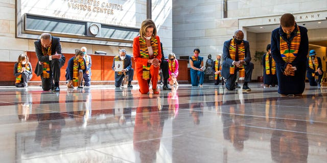 House Speaker Nancy Pelosi of Calif., center, and other members of Congress, kneel and observe a moment of silence at the Capitol's Emancipation Hall, Monday, June 8, 2020, on Capitol Hill in Washington, reading the names of George Floyd and others killed during police interactions. Democrats proposed a sweeping overhaul of police oversight and procedures Monday, an ambitious legislative response to the mass protests denouncing the deaths of black Americans at the hands of law enforcement. (AP Photo/Manuel Balce Ceneta)
