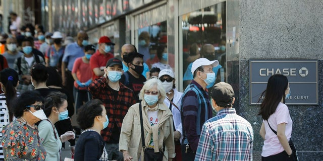People wear protective masks outside a bank in the Queens borough of New York City, June 8, 2020. (Associated Press)