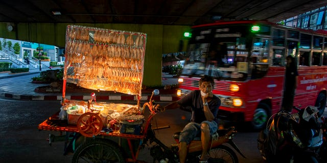 A mobile food vender looks for customers in Bangkok, Thailand, Tuesday, June 9, 2020.