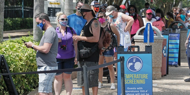 Guests wait in line to have their temperature taken before entering SeaWorld as it reopens with new safety measures in place, Thursday, June 11, 2020, in Orlando, Fla. The park had been closed since mid-March to stop the spread of the coronavirus. (AP Photo/John Raoux)