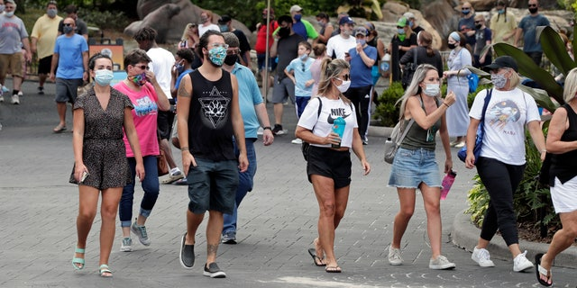 Guests wearing masks stroll through SeaWorld as it reopened with new safety measures in place Thursday, June 11, 2020, in Orlando, Fla. (AP Photo/John Raoux)