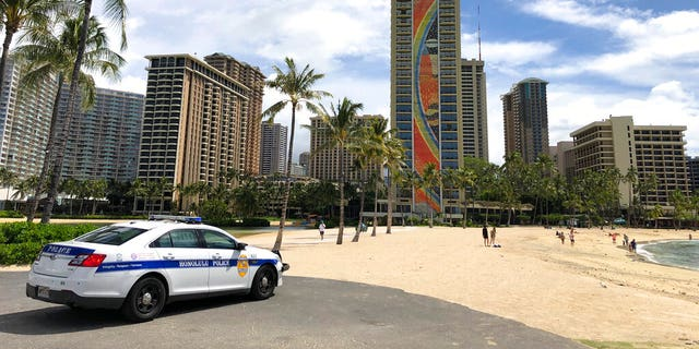 "In this March 28 photo a police officer arrives to tell people to leave Waikiki Beach in Honolulu. A Facebook group with more than 2,000 people called the ""Hawaii Quarantine Kapu Breakers,"" is focused on finding people who violate Hawaii's 14-day quarantine on travelers arriving to the state. Kapu is a Hawaiian word that means laws or rules. The group is (AP Photo/Caleb Jones,File)"