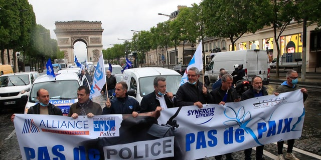 French police unionists demonstrate with a banner reading
