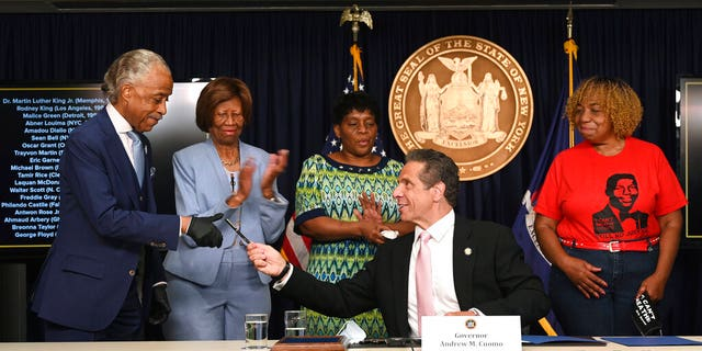 New York Governor Andrew M. Cuomo, center, hands a pen to Rev. Al Sharpton after signing into law, Friday, June 12, 2020, in New York, a sweeping package of police accountability measures that received new backing following protests of George Floyd's killing. (Kevin P. Coughlin, Office of New York Governor Andrew M. Cuomo via AP)