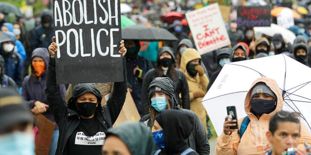 "A protester holds a sign that reads ""Abolish Police"" during a ""Silent March"" against racial inequality and police brutality that was organized by Black Lives Matter Seattle-King County, Friday, June 12, 2020, in Seattle. Hundreds of people marched for nearly two miles to support Black lives, oppose racism and to call for police reforms among other issues. (AP Photo/Ted S. Warren)"