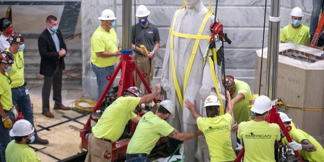 Workers prepare to remove the Jefferson Davis statue from the Kentucky state Capitol in Frankfort, Ky., on June 13. (Ryan C. Hermens/Lexington Herald-Leader via AP)