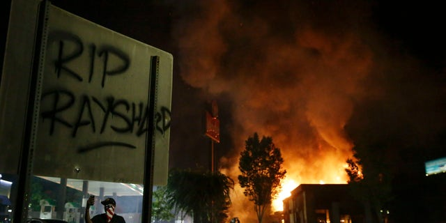 """""""RIP Rayshard"""" is spray painted on a sign as as flames engulf a Wendy's restaurant during protests Saturday, June 13, 2020, in Atlanta. The restaurant was where Rayshard Brooks was shot and killed by police Friday evening following a struggle in the restaurant's drive-thru line. (Associated Press)"""