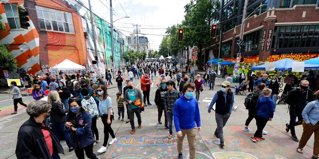 """Visitors walk near a sign that reads """"Welcome to CHOP,"""" Sunday, June 14, 2020, inside what has been named the Capitol Hill Occupied Protest zone in Seattle. . (AP Photo/Ted S. Warren)"""
