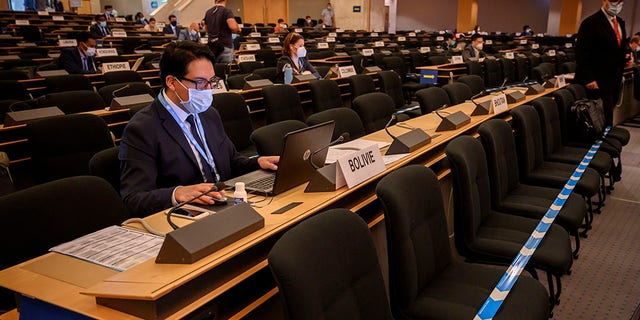 Delegates wearing protective face masks attend the resuming of the UN Human Rights Council session after the break-in March over the coronavirus pandemic, on Monday, 15 June 2020, in Geneva.