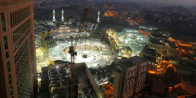 In this March 7, 2020 file photo, the sun sets at the site of the Grand Mosque, in the Muslim holy city of Mecca, Saudi Arabia, as authorities emptied Islam's holiest site for sterilization over fears of the new coronavirus. (AP Photo/Amr Nabil, File)