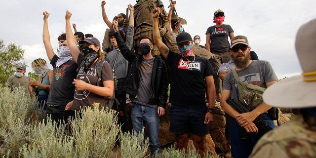 Demonstrators climb the statue of Don Juan de Onate in Old Town in Albuquerque, N.M. (Adolphe Pierre-Louis/The Albuquerque Journal via AP)