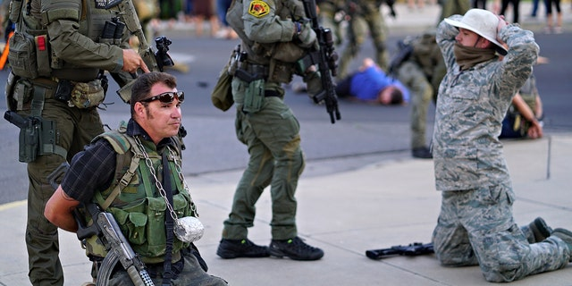 Albuquerque police detain members of the New Mexico Civil Guard, an armed civilian group, following the shooting of a man during a protest over a statue of Spanish conquerer Juan de Oñate on Monday, June 15, 2020, in Albuquerque, N.M. (Adolphe Pierre-Louis/The Albuquerque Journal via AP)