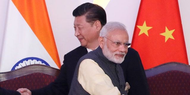 In this Oct. 16, 2016, file photo, Indian Prime Minister Narendra Modi, front and Chinese President Xi Jinping shake hands with leaders at the BRICS summit in Goa, India. (AP Photo/Manish Swarup, File)