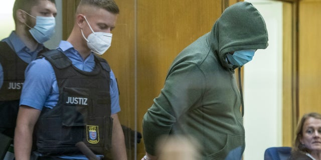 """Police officers lead defendant Markus H., right, into the court room in Frankfurt, German, June 16, 2020. The Higher Regional Court begin hearing the case against two far-right extremists accused of killing the regional politician Walter Luebcke of Merkel""""s Christian Democratic Union party.(Thomas Lohnes/Pool via AP)"""