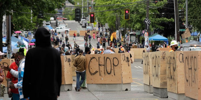 Cement and wood barricades bear the name CHOP, Tuesday, June 16, 2020, inside what has been named the Capitol Hill Occupied Protest zone in Seattle.