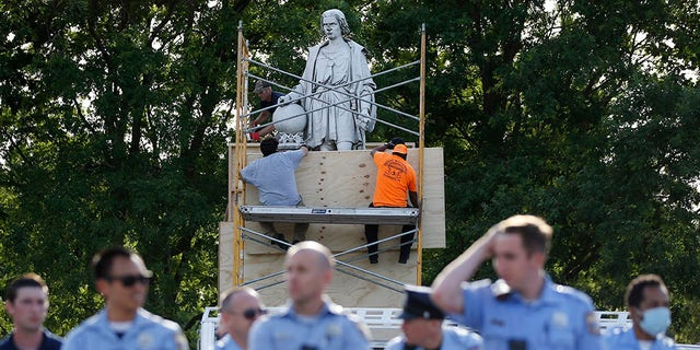 City workers cover the statue of Christopher Columbus at Marconi Plaza, Tuesday, June 16, 2020, in the South Philadelphia neighborhood of Philadelphia. (AP Photo/Matt Slocum)