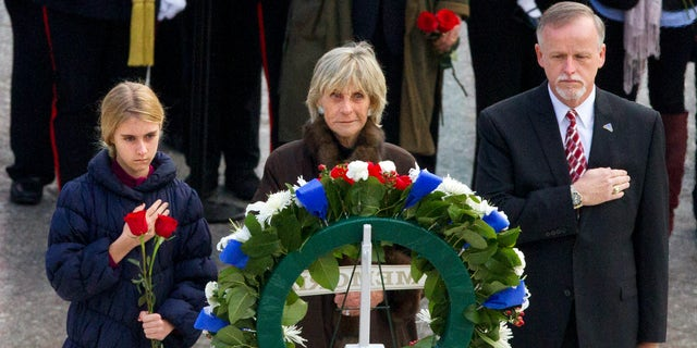 FILE - In this Nov. 22, 2013 file photo, An unidentified girl, left, holds a rose during a wreath laying ceremony with former Ambassador to Ireland Jean Kennedy Smith, center, and Patrick Hallinan, executive director of Army National Military Cemeteries, at the grave of John F. Kennedy at Arlington National Cemetery, in Arlington, Va. Jean Kennedy Smith, the youngest sister and last surviving sibling of President John F. Kennedy, died at 92, her daughter confirmed to The New York Times, Wednesday, June 17, 2020. (AP Photo/Jacquelyn Martin)