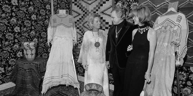 FILE - In this Nov. 26, 1974 file photo, Marlon Brando, center, Ethel Kennedy, left, and Jean Kennedy Smith stand amid Native American Indian artifacts at the American Indian Development Dinner at the Waldorf-Astoria Hotel in New York. Jean Kennedy Smith, the youngest sister and last surviving sibling of President John F. Kennedy, died at 92, her daughter confirmed to The New York Times, Wednesday, June 17, 2020. (AP Photo/Richard Drew, File)