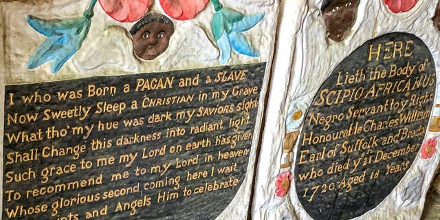 Casts of the headstone and footstone of an enslaved African man, in the entrance to St Mary's church. The Grade II-listed, brightly painted memorial to Scipio Africanus have been smashed and a message was scrawled in chalk on flagstones nearby. (Ben Birchall/PA via AP)