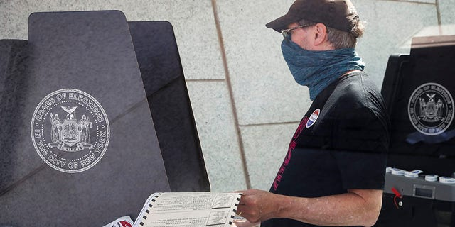 FILE - In this June 16, 2020, file photo, a voter casts their ballot at a polling station inside the Brooklyn Museum as early voting continues in the Brooklyn borough of New York. (AP Photo/John Minchillo, File)