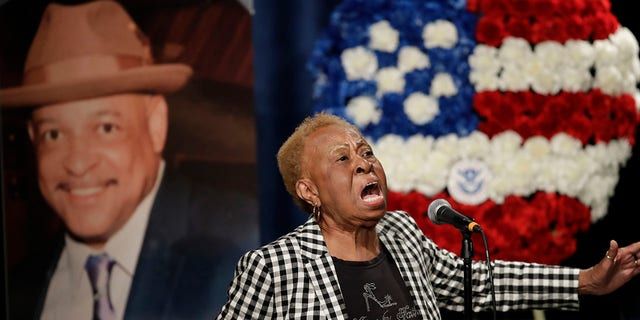 Janie Taylor sings beside a photo of Federal Protective Services Officer Dave Patrick Underwood on Friday, June 19, 2020, in Pinole, Calif. Underwood was fatally shot as he was guarding the Ronald V. Dellums Federal Building in Oakland, Calif., amid protests on May 29. (Associated Press)