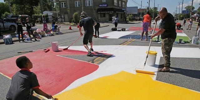 "Local artists paint ""Black Lives Matter"" spanning three blocks on East 93rd Street in Cleveland, on Saturday. (John Kuntz/Cleveland.com via AP)"