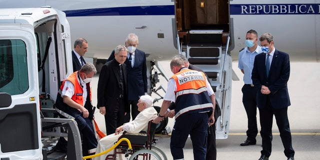 Emeritus Pope Benedict XVI, center, is taken out of an ambulance as he arrives for his departure at Munich Airport in Freising, Germany, Monday June 22, 2020. Emeritus Pope Benedict XVI is returning to the Vatican after a four-day visit to Germany to visit his ailing elder brother. (Sven Hoppe/dpa via AP)