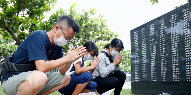 """Members of a bereaved family pray in front of a """"Cornerstone of Peace"""" monument wall on which the names of all those who lost their lives, both civilians and military of all nationalities in the Battle of Okinawa are engraved, at the Peace Memorial Park in Itoman, Okinawa, Japan, Tuesday, June 23, 2020. (Kyodo News via AP)"""